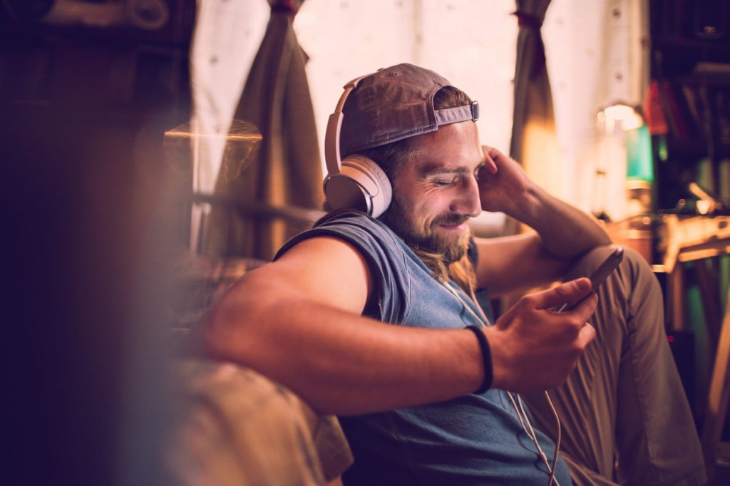 Mann hører på msuikk fra smarttelefon